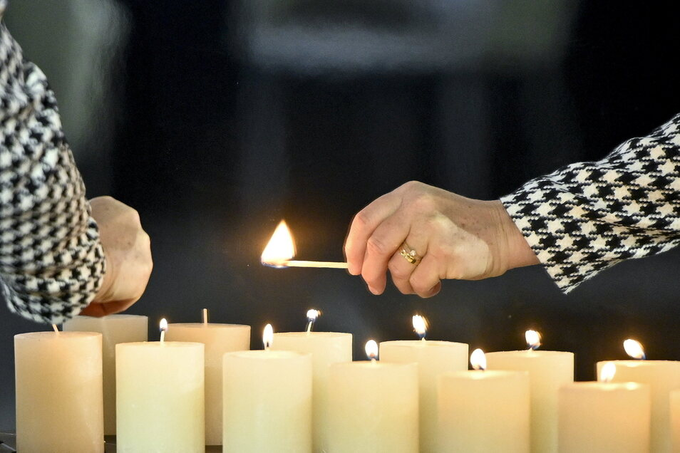 Angehörige zünden bei einer Gedenkveranstaltung in der Aula der Wiener Akademie der Wissenschaften, wo den Opfern der Corona-Pandemie gedacht wird, Kerzen an.