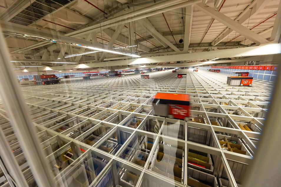 Roboter greifen in dem hoch automatisierten Ausllieferungslager von Bike 24 auf die Waren zu.