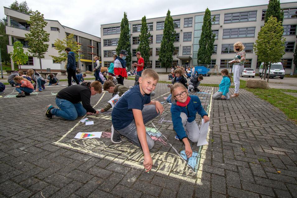 """Die neuen 5. Klassen haben den Schulhof des Martin-Luther-Gymnasiums Hartha gestaltet. Philipp (vorn links) und Timo sowie ihre Kameraden aus der 5a malen das """"M"""" aus."""