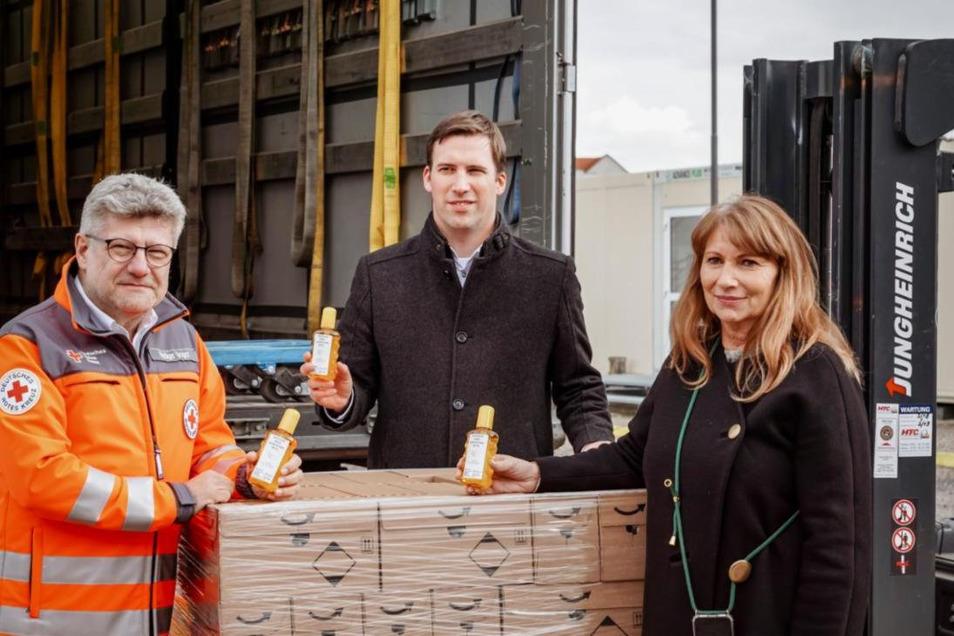 Stephan Roelen (links), Werksleiter von Beiersdorf in Waldheim, hat die Flaschen mit Handdesinfektion Rüdiger Unger, dem Chef des DRK-Landesverbandes Sachsen, übergeben. Mit dabei war Sachsens Gesundheitsministerin Petra Köpping.