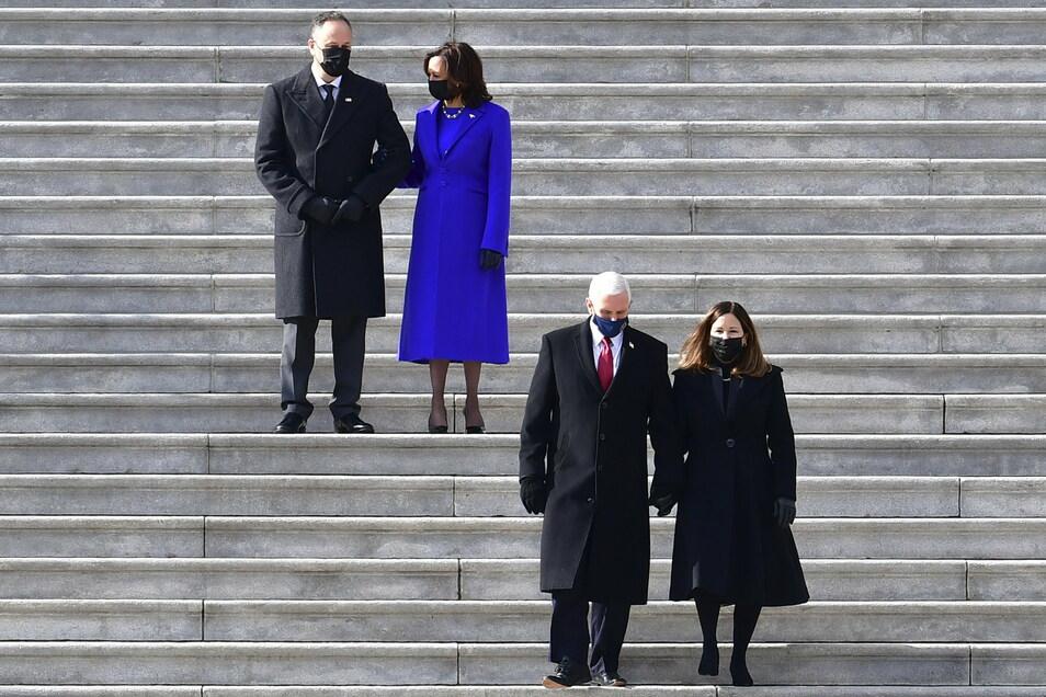 US-Vizepräsidentin Kamala Harris und ihr Ehemann Doug Emhoffl (l) sehen zu wie der ehemalige Vizepräsident Mike Pence (2.v.r.) und seine Frau Karen Pence das Kapitol nach der Amtseinführung von US-Präsident Joe Biden verlassen.
