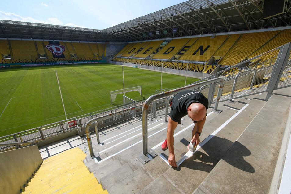 Auch der Stehplatzbereich K-Block im Rudolf-Harbig-Stadion ist geöffnet. Ein Mitarbeiter klebt die Bereiche für die Infektionsgemeinschaften ab.