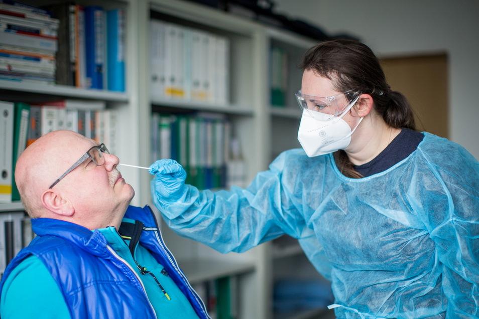 Mirjam Mickel nimmt bei Christian Mickel einen Nasenabstrich. Das Gehäusebauunternehmen CooolCase betreibt für seine Mitarbeiter ein Minitestzentrum mit medizinisch geschultem Personal und nutzt die App Pass4all.