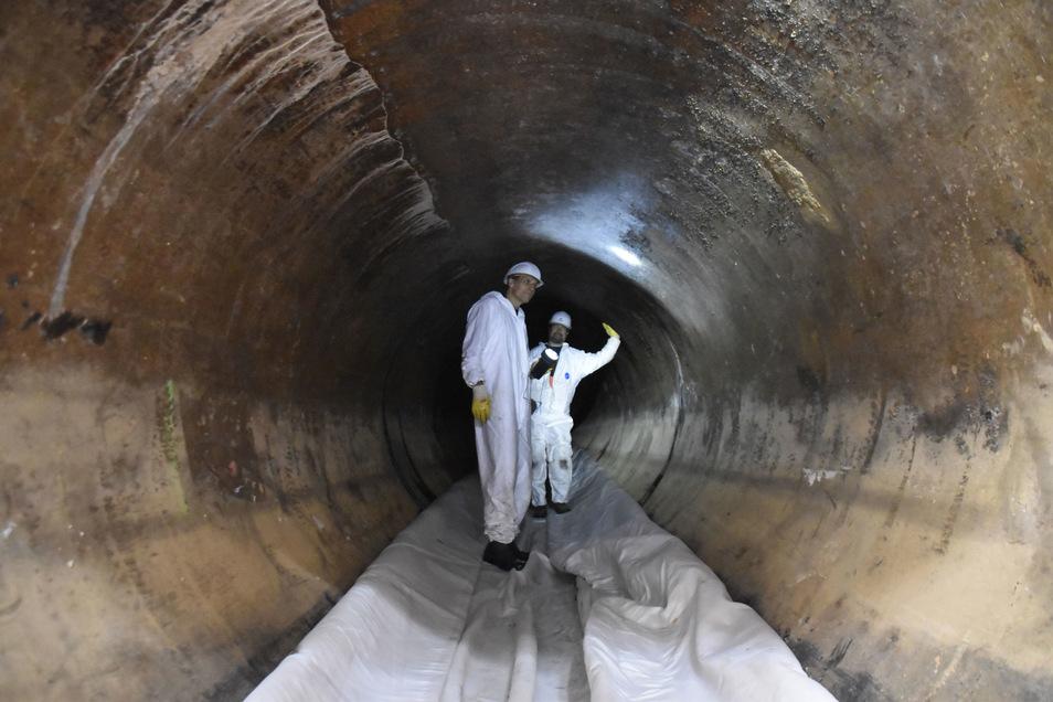 Der erste Schlauch ist im Abwassertunnel. Die Kanalsanierer Frank Grüssing (vorn) und Eric Ulrich begutachten die 113 Jahre alte Röhre, bevor die Schläuche mit Wasserdruck gegen die Wand gepresst werden.