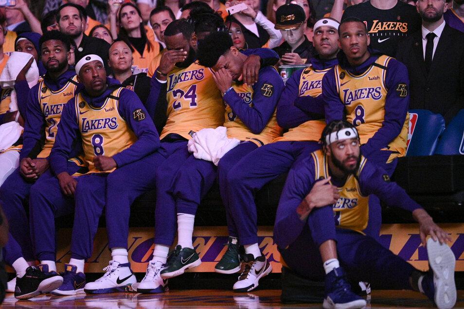LeBron James (M, l) und Quinn Cook (M, r) von den Los Angeles Lakers während eines Video-Beitrags über Kobe Bryant ihre Hände vors Gesicht.