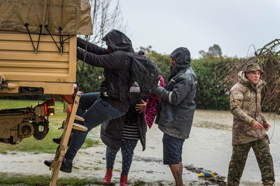 Mitarbeiter der neuseeländischen Streitkräfte helfen einer Familie bei der Evakuierung in der Nähe von Ashburton.