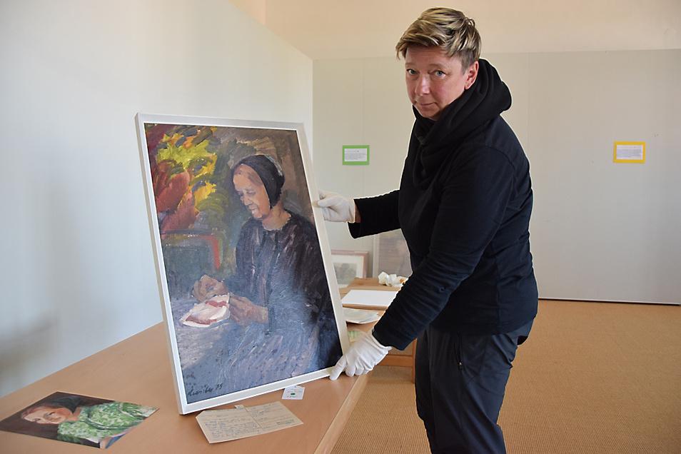 Kerstin Noack zeigt ein Gemälde des tschechischen Malers Juraj Kresila, das vor dem Umzug des Depots digital inventarisiert werden muss.