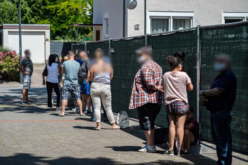 Menschen stehen Schlange beim gratis Coronavirus-Test für die Bevölkerung am Carl-Miele-Berufskolleg in Gütersloh.