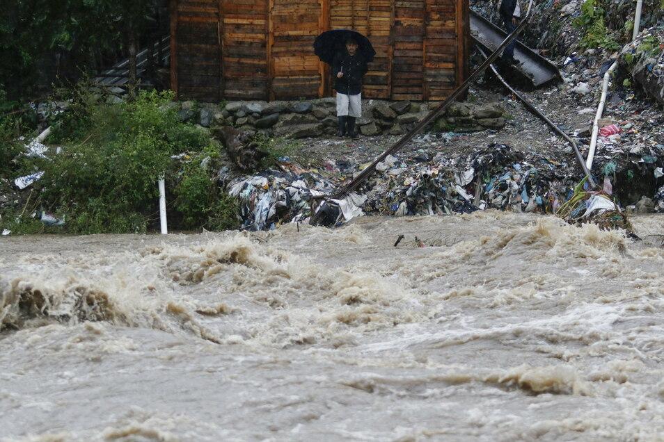 Ein Mann beobachtet mit einem Regenschirm in der Hand die wegen der Überschwemmungen starken Strömungen des Rio Bermejo.