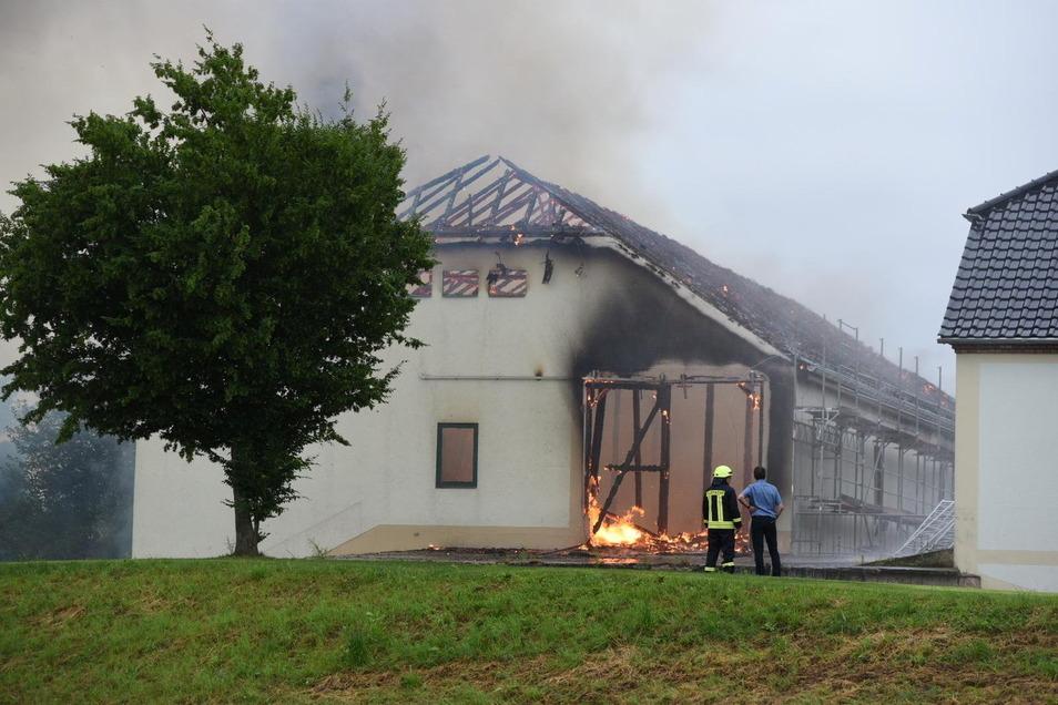 """Es ist nichts mehr zu retten: Eine Scheune der """"Wundervollen Weihnachtswelt"""" in Strocken steht in Vollbrand. Bürgermeister Jörg Burkert (rechts) spricht mit der Feuerwehr über das Vorgehen der Einsatzkräfte."""