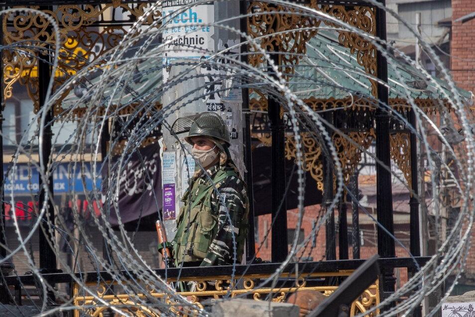 Ein paramilitärischer Soldat steht vor einem geschlossenen Markt. Nach dem Tod eines bekannten Separatistenführers in der indischen Unruheregion Kaschmir an der Grenze zu Pakistan, hat die Regierung das Internet gesperrt sowie das Mobilnetz und die Bewe