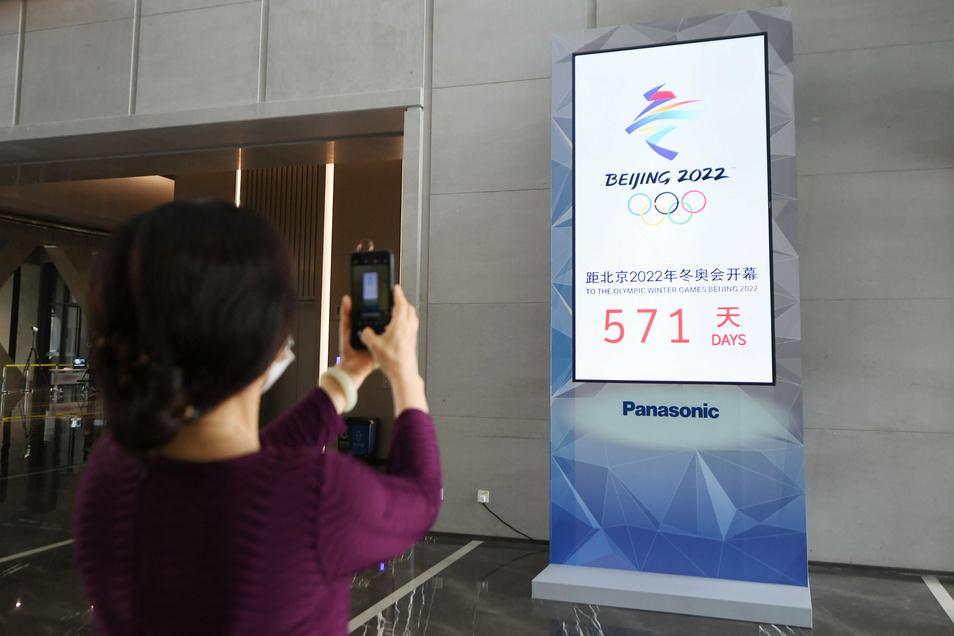 Eine Frau fotografiert eine Countdown-Anzeige für die Olympischen Winterspiele in Peking 2022