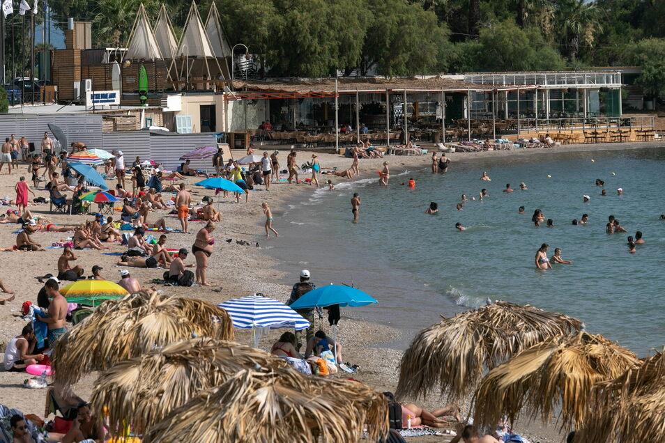 Menschen bei Athen genießen das warme Wetter am Strand. Griechenland soll in dieser Woche von einer Hitzewelle erfasst werden.