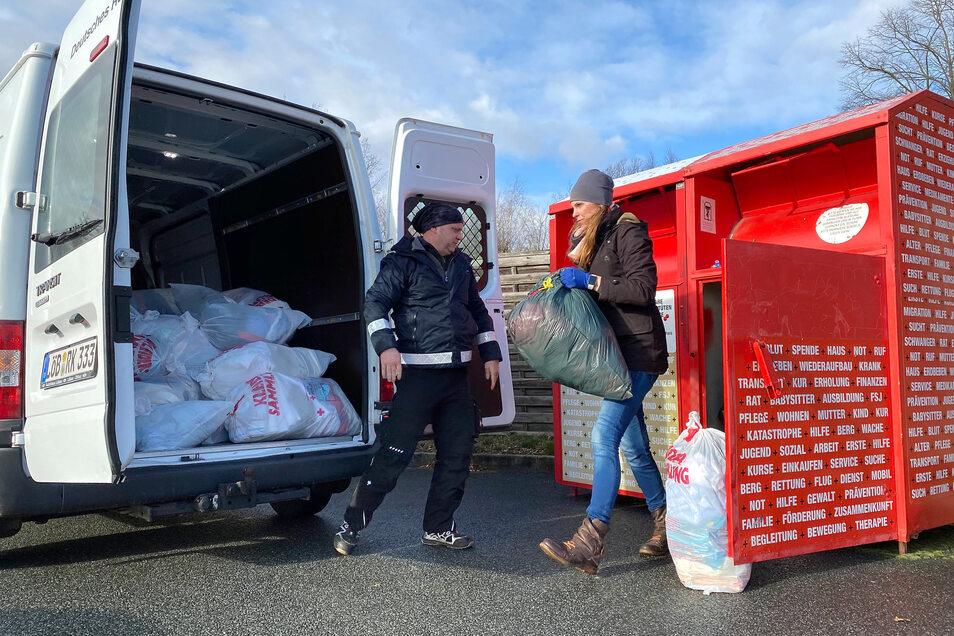 Ronny Albert vom DRK und Romy Altmann-Kühr leeren einen Sammelcontainer in Oppach.