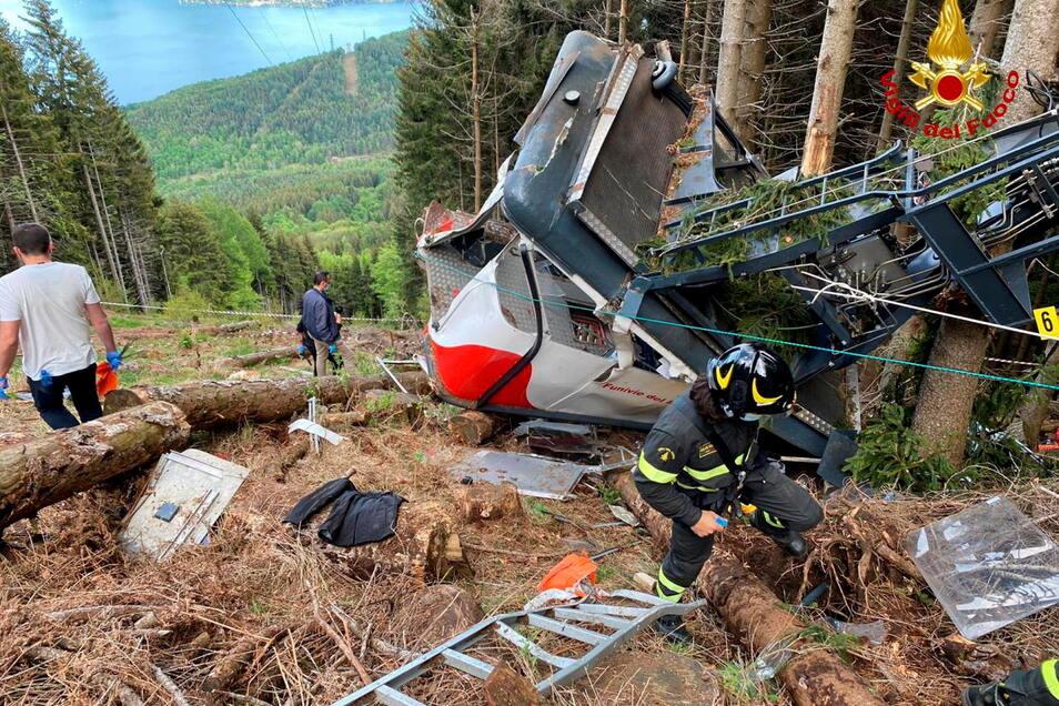 Rettungshelfer arbeiten nach dem Unglück am Wrack der Seilbahngondel.
