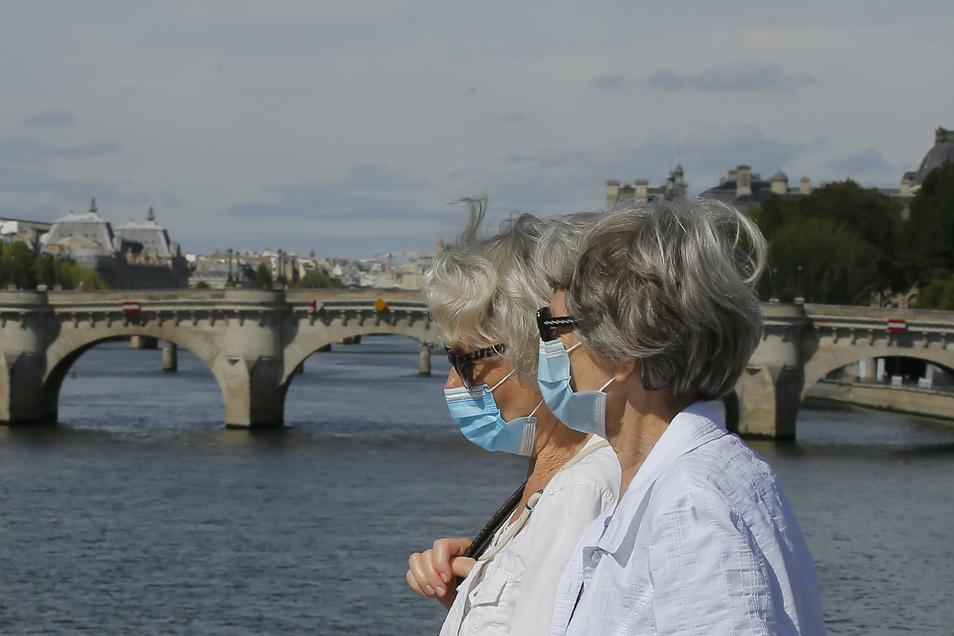 Zwei Passantinnen mit Mundschutz spazieren über eine Brücke in Paris.