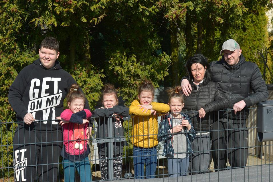 Die Vierlinge Jasmin, Laura, Kim und Sophie (von links) stehen mit Bruder Lucas und den Eltern Janett und Marcus hinterm Zaun im Garten ihres Zuhauses in Beucha bei Leipzig. Foto: Volkmar Heinz
