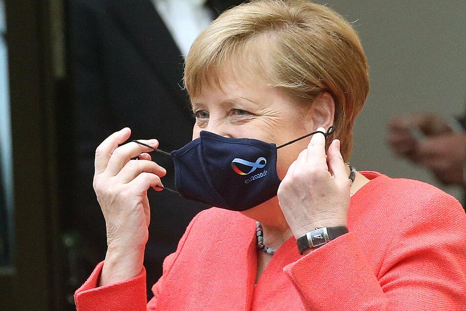 Angela Merkel wurde im Bundesrat erstmals offiziell mit einem Mund-Nase-Schutz fotografiert. Auf der schwarzen Maske war das Logo der deutschen EU-Ratspräsidentschaft zu sehen.