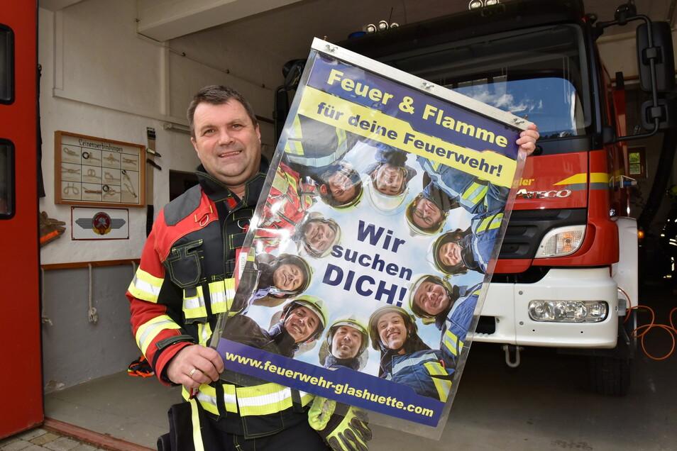 Stadtwehrleiter Veith Hanzsch zeigt ein Plakat, mit dem die Glashütter Feuerwehr aktuell Mitstreiter sucht.