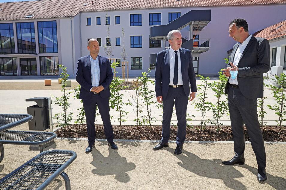 Drei Herren im Anzug: Stadtwerke-Chef René Röthig, Regionalentwicklungs-Minister Thomas Schmidt (CDU) und Riesas OB Marco Müller (CDU) auf dem Hof der Oberschule Am Merzdorfer Park, die gerade umgebaut wird.