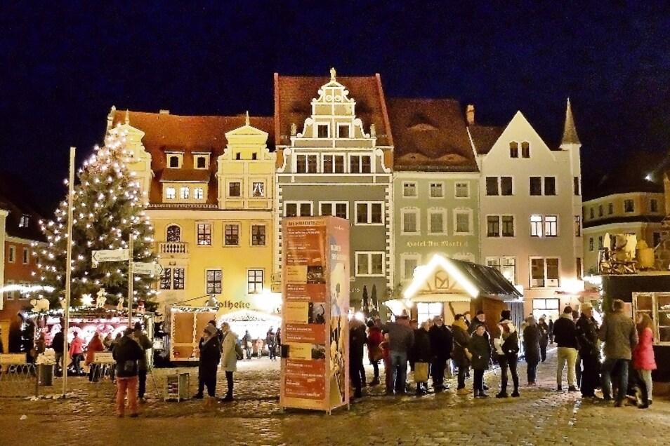 Sonnabendabend auf dem Meißner Markt. Buden um den Weihnachtsbaum bieten Kunsthandwerk und Weihnachtsleckereien. Die Gasthäuser verkaufen Glühwein to go.