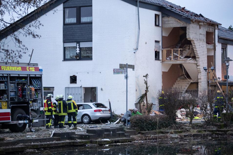 Feuerwehrleute stehen vor dem von einer Gasexplosion stark beschädigten Haus. Ein Feuerwehrmann kam ums leben und drei weitere wurden verletzt,