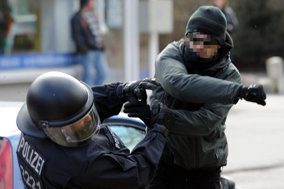 Ein gewalttätiger Demonstrant schlägt einen Polizeibeamten nieder.