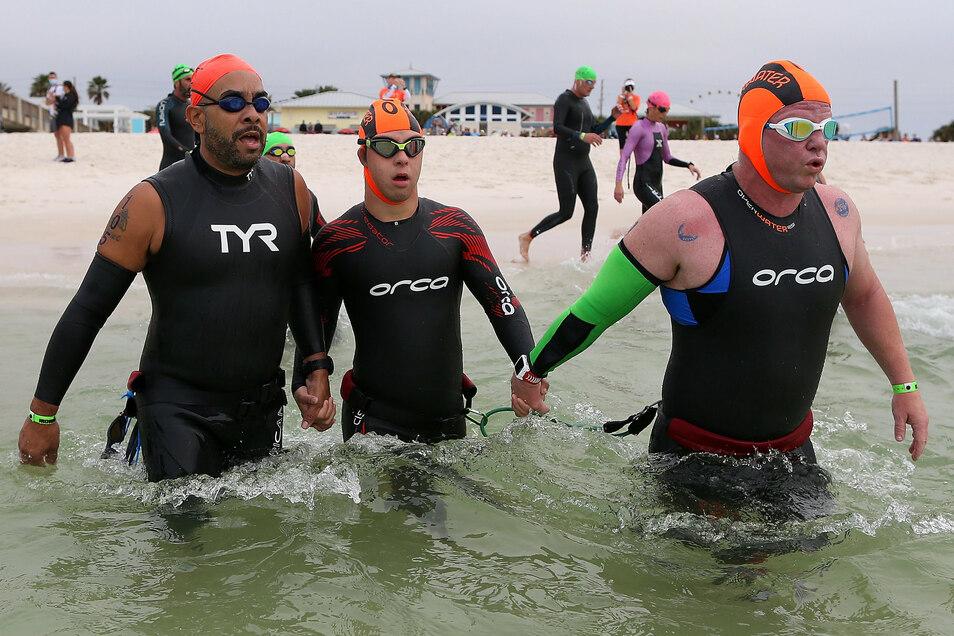 Coach Daniel Grieb (r.) war auch dabei, als es für Chris Nikic (Mitte) beim Start ins Wasser ging.