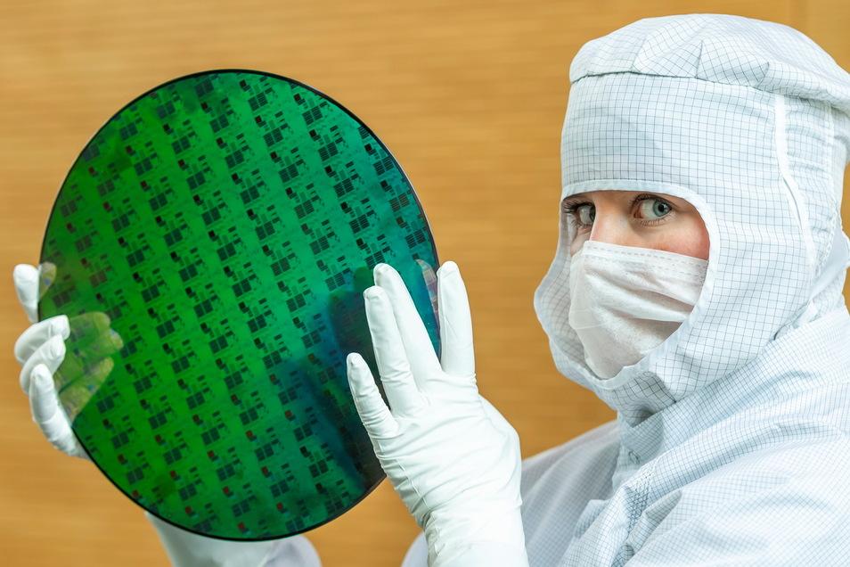 Nachschub an Mikrochips aus Sachsen in Sicht: In der Globalfoundries-Fabrik zeigt eine Mitarbeiterin in Reinraumkleidung eine Siliziumscheibe, auf der durch Belichten und Ätzen viele Mikrochips entstanden sind.