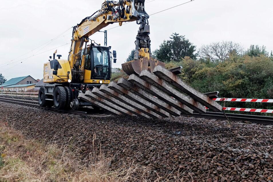 Ein Bagger auf Schienen reißt ein Teil des Gleises bei Glaubitz heraus.