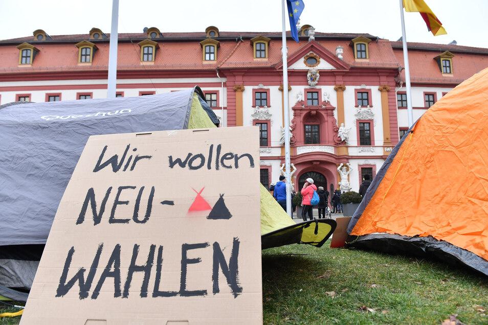"""In Erfurt stehen Zelte und ein Plakat mit der Aufschrift """"Wir wollen Neu-Wahlen"""" vor der Staatskanzlei."""