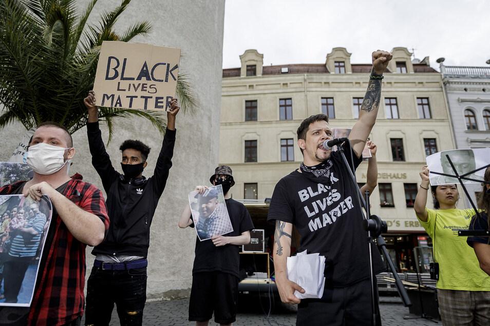 Organisatoren und Teilnehmer der Demo zeigen Fotos von Opfern rassistischer Gewalt.