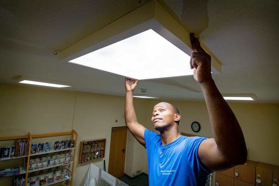 Bongani Medikane baut die neuen Leuchten in der Stadtbibliothek an. Der Einbau erfolgt bei laufendem Betrieb. Die Stadt ersetzt damit 25 Jahre alte Neonleuchten.