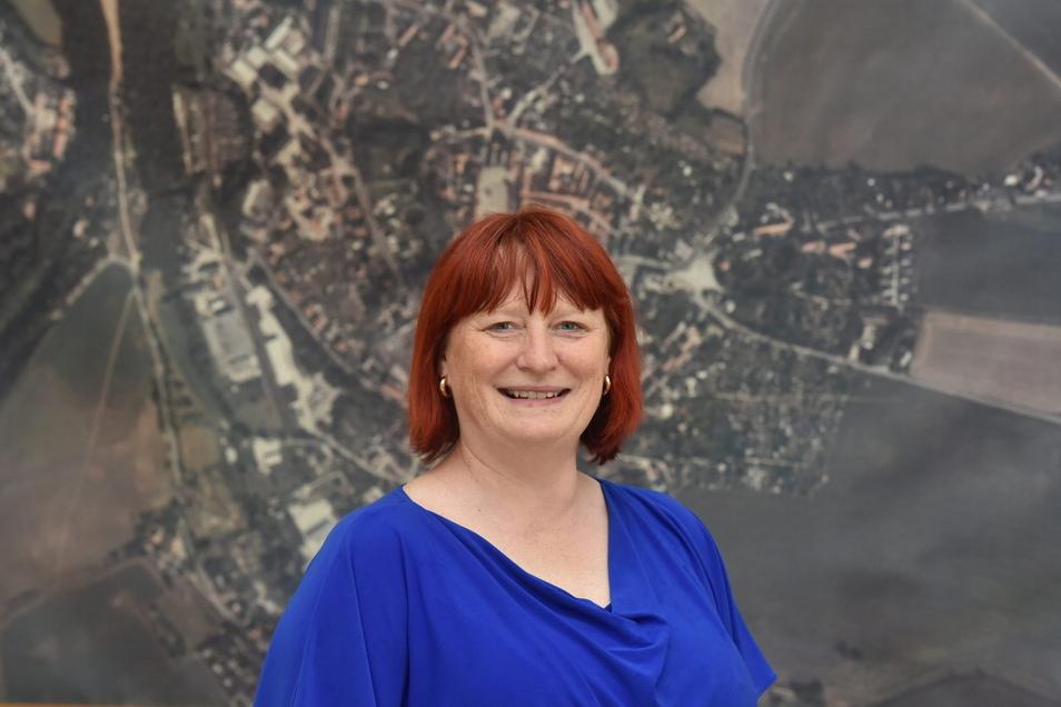 Oberbürgermeisterin Kerstin Körner steht vor einem Luftbild der Stadt, das über 20 Jahre alt ist. Für solche Zeiträume will sie auch in die Zukunft planen.