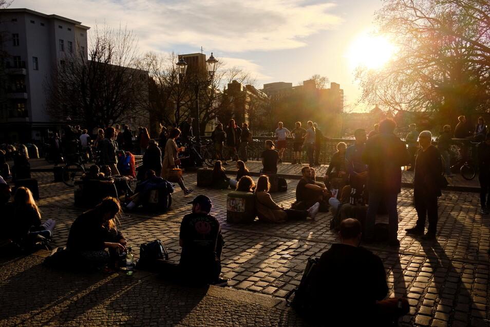 Zahlreiche Menschen sitzen, ohne Schutzmasken und zum Teil ohne den vorgeschriebenen Mindestabstand einzuhalten, im Licht der untergehenden Sonne auf der Admiralbrücke, einem beliebten Treffpunkt junger Menschen in Berlin-Kreuzberg.