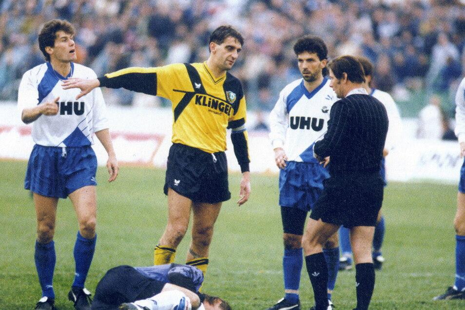 Als Kapitän hat sein Wort Gewicht, aber Schiedsrichter Klaus Scheurell lässt sich auf keine Diskussion mit Ralf Minge ein. Dynamo trennt sich im Heimspiel torlos von Hansa Rostock - am Ende der Saison steigen beide Ost-Teams in die Bundesliga auf.