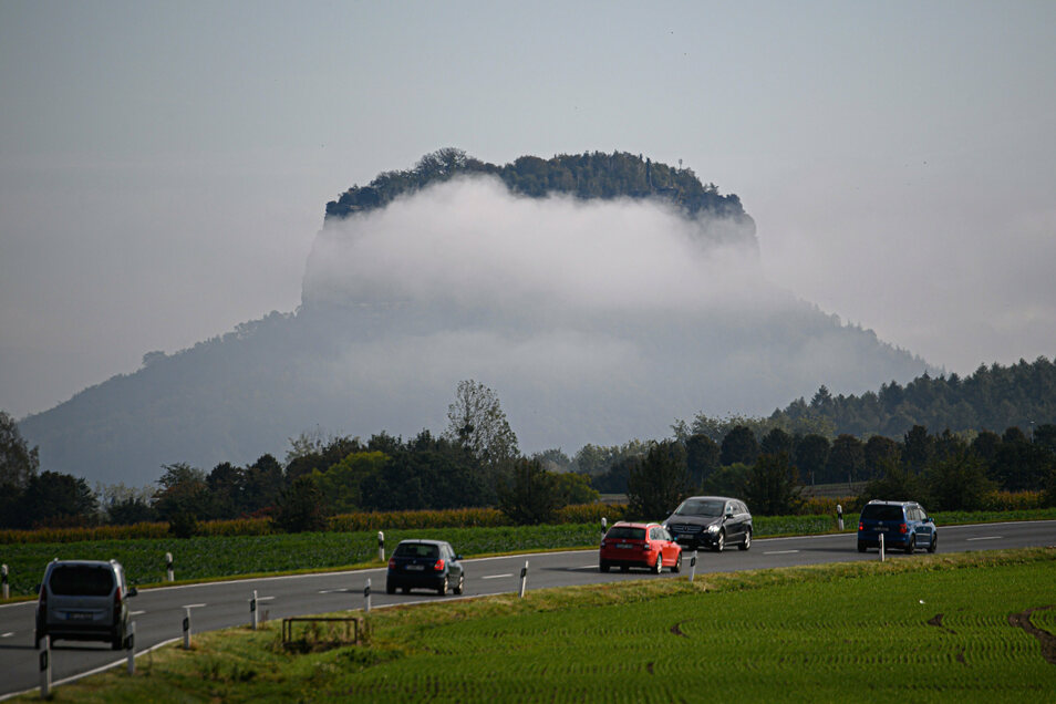 Autos fahren die Bundesstraße B172 in Richtung der Sächsischen Schweiz vor dem Lilienstein im Nebel entlang.