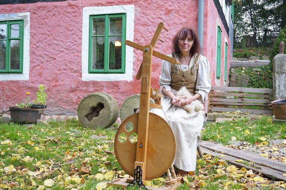 Renata Šoltová am Spinnrad vor ihrem Haus in Krásný Les (Schönwald). Von der Schafwolle bis zum Kleidungsstück entsteht alles in traditioneller Handarbeit.