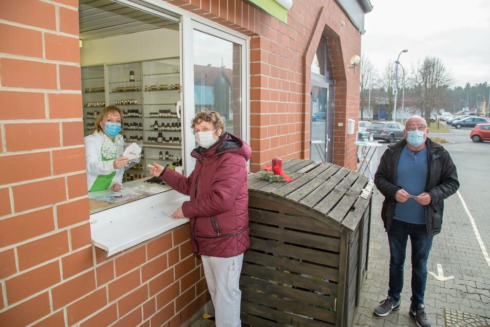 An der Linden-Apotheke in Niesky geben Ivonne Gärtner (links) und ihre Mitarbeiterinnen die FFP2-Masken am Fenster aus. Erika Reinhold hilft als Mitarbeiterin der Apotheke den Kunden beim Ausfüllen der Zettel, so auch Andreas Krüger (rechts):