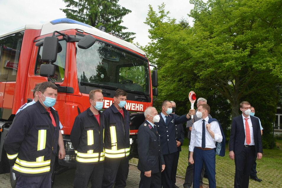 Gruppenfoto der Feuerwehr Friedersdorf mit Ministerpräsident, Bürgermeister (verdeckt), Innenminister und neuem Fahrzeug.