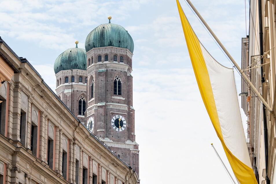 Eine Fahne mit den Farben der katholischen Kirche, gelb und weiß, ist vor den Türmen der Münchner Frauenkirche zu sehen.
