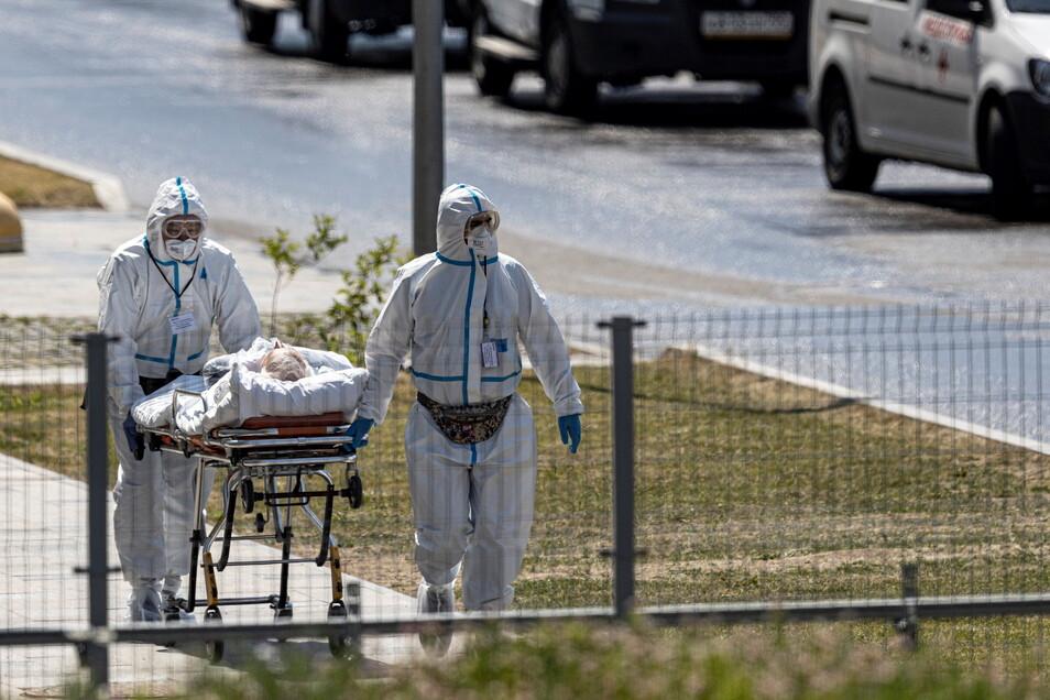 Medizinisches Personal in Schutzkleidung transportiert einen Patienten, bei dem der Verdacht auf eine Corona-Infektion besteht, in einem Krankenbett auf dem Gelände des Krankenhauses Kommunarka.