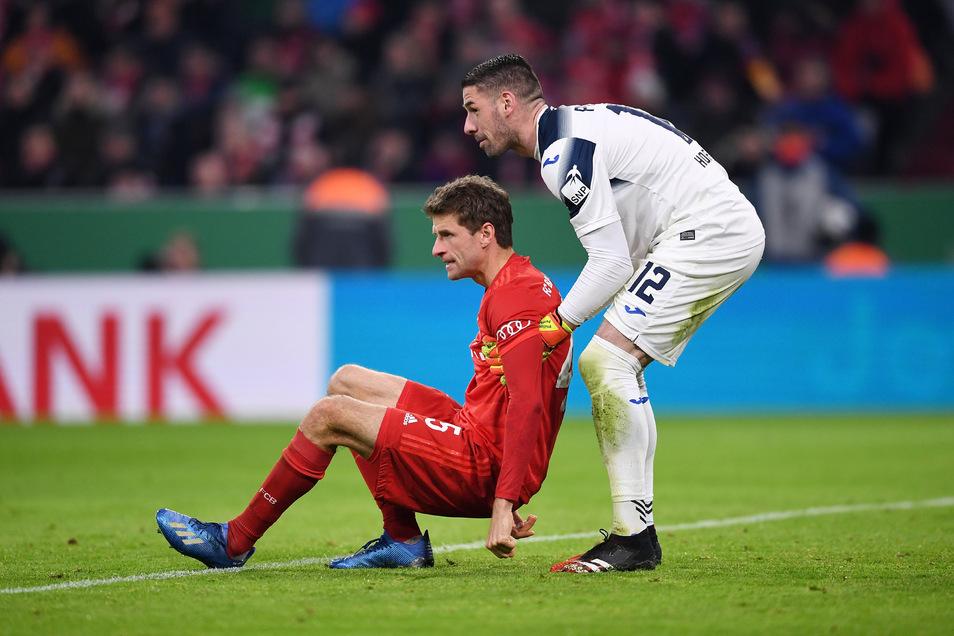 Wenn es sein muss, hilft er auch den Stars wieder auf die Beine: Hoffenheims Torwart Philipp Pentke (r.) greift Bayern Münches Thomas Müller unter die Arme.