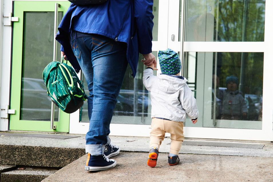 Ein Kind und seine Mutter gehen zum Eingang einer Kita. In Waldheim soll die Betreuung im Kindergarten und der Krippe teurer werden.