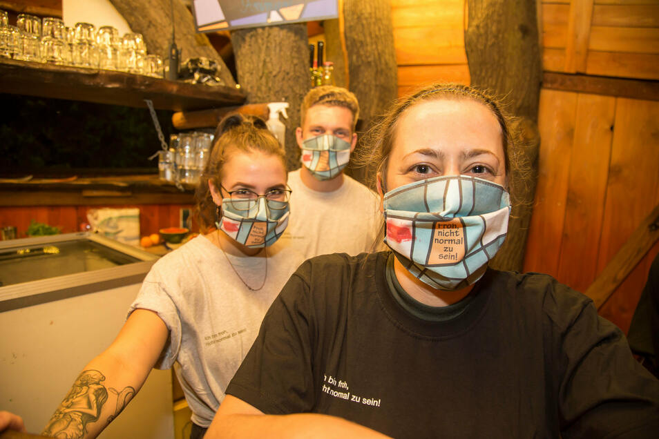 """Die Mitarbeiter - wie hier das Team der """"Fionas Elfenbar"""" - trugen das Motto """"Froh, nicht normal zu sein"""" buchstäblich im Gesicht, als Sicherheitsmaßnahme. Diese bunten Masken mit dem typischen Muster bekamen auch die Besucher mit ihrem Ticket am Einlass."""