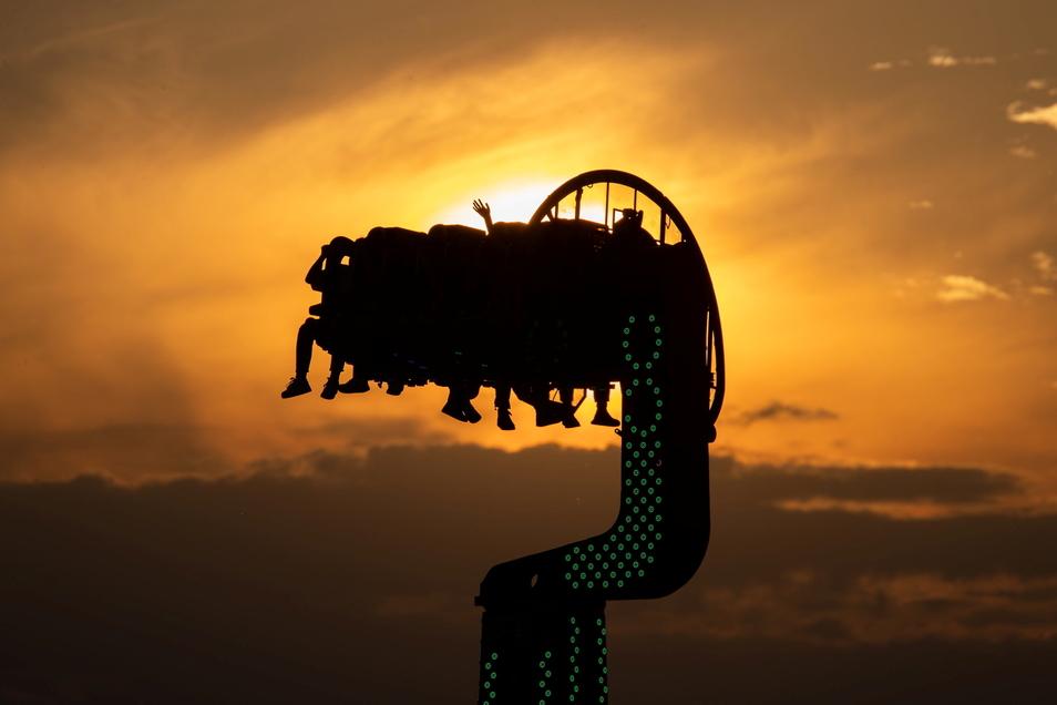 Besucher eines Freizeitparks in Nürnberg sitzen in der Abendsonne in einem Fahrgeschäft. Lockerungen der Corona-Beschränkungen können zum Anstieg der Neuinfektionen beigetragen haben.