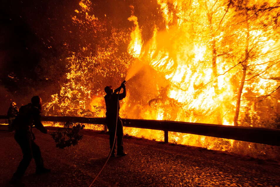 Flammenhölle bei Athen: Freiwillige Helfer unterstützten einen Feuerwehrmann bei den Löscharbeiten.