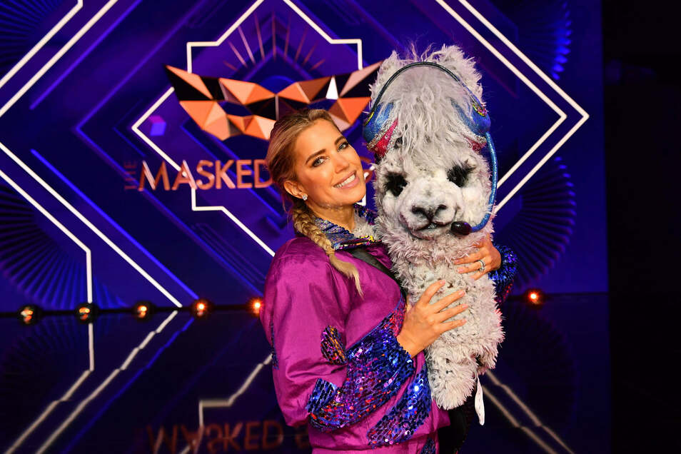 """TV-Moderatorin Sylvie Meis hält die Maske der Figur des Alpakas in der dritten Show der dritten Staffel des Gesangswettbewerbs. Bei """"The Masked Singer"""" singen Prominente in aufwendigen Bühnenkostümen um die Wette."""