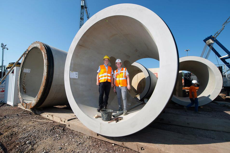 Die Projektleiter Norbert Gassel (Drewag, l.) und Maik Borrmann stehen in einem der letzten Tunnelrohre, die noch in die Grube unweit der Marienbrücke gehoben werden müssen. © René Meinig
