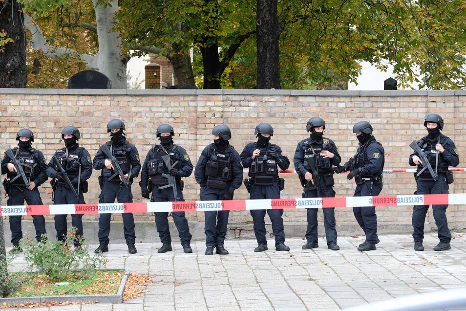 Polizisten sichern den Bereich am jüdischen Friedhof in Halle ab. Bei Schüssen sind zwei Menschen getötet worden.